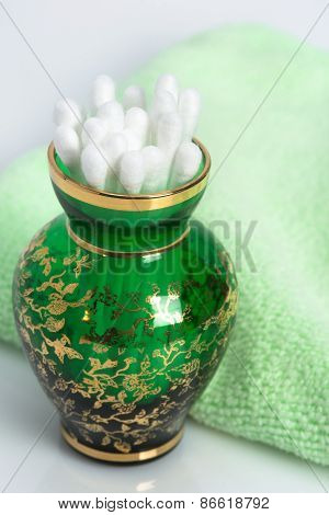 Cotton Swabs In A Green Glass Vase