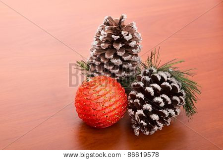 Two fir cones and a decorative bulb on a wooden table