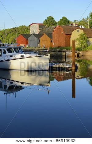 Boat Reflecting in Calm Water at Dock