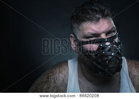 Adult agressive man in muzzle in the dark