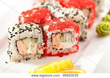 Japanese Cuisine - Sushi Roll with Fried Salmon, Cheese and Cucumber inside. Sesame and Tobiko outside
