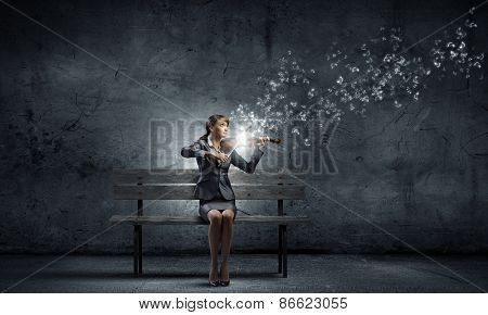 Young businesswoman sitting on bench and playing violin