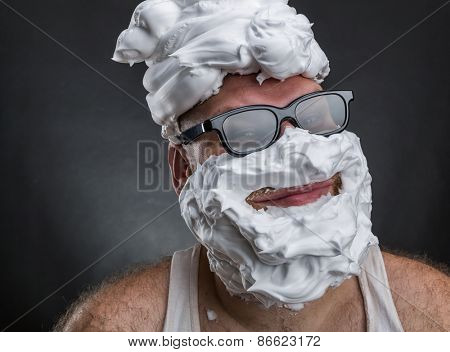 Strange smiling man in glasses with shaving foam on his face and on his head closeup