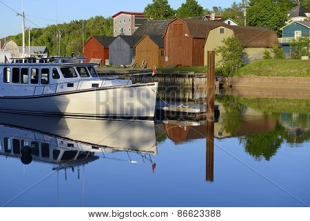 Fishing Boat Reflecting in Smooth Water at Sunset