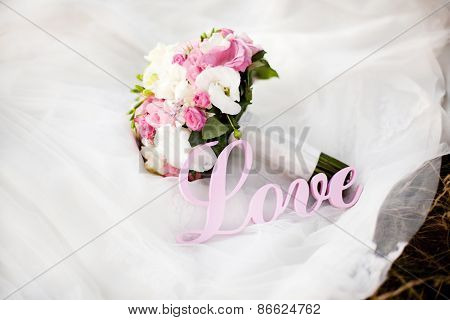 Pink And White Wedding Bouquet On The Dress With Letters