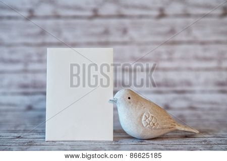 White Bird Figurine with Vertical Blank Card on Rustic White Wooden Background with Copy Space for Personal Message or Greeting