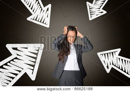 Frustrated Young Businesswoman Tearing her Hair Surrounded by Conceptual White Arrows on Abstract Gray Gradient Background.