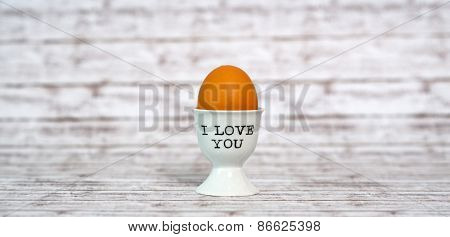 One Brown Egg in a White Porcelain Cup with I love You Texts on a Wooden Table with Abstract Background.