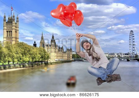 Young man flying on balloons with The Palace of Westminster, London, UK in background