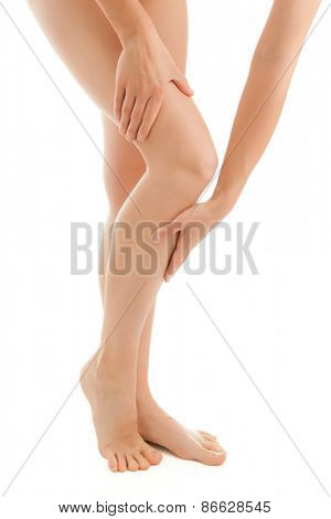 Woman massaging legs standing on white background