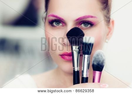 The Makeup Artist Holds Powder Brushes
