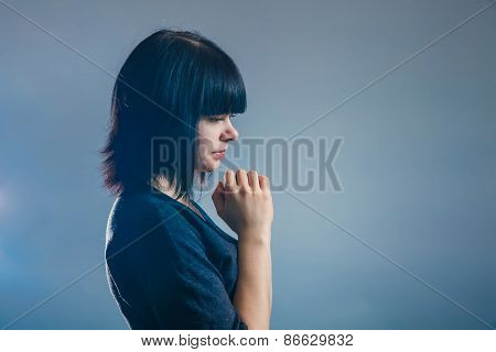 European-looking girl brunette in black jacket folded her hands