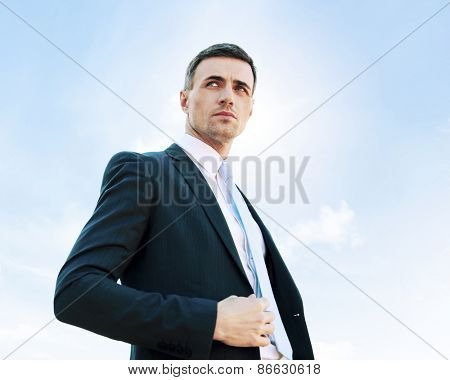 Portrait of a thoughtful businessman on blue sky background