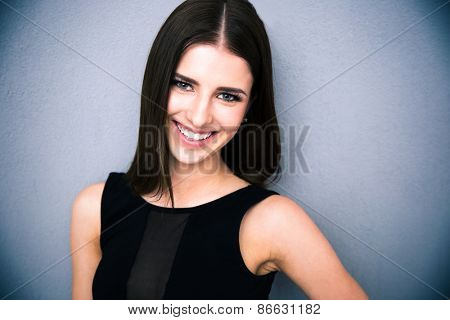 Portrait of a smiling attractive looking at the camera. Wearing black dress. Posing over grey background
