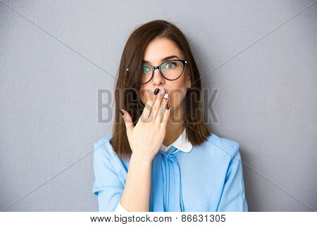 Businesswoman covering her mouth with her hands. Wearing in blue shirt and glasses. standing over gray background. Looking at camera