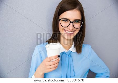 Portrait of a happy businesswoman holding cup with coffee over gray background. Wearing in blue shirt and glasses. Looking at camera