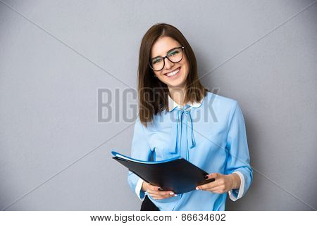 Smiling businesswoman standing with folders over gray background. Wearing in blue shirt and glasses. Looking at camera
