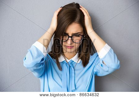 Young businesswoman with headache over gray background. Touching her head. Wearing in blue shirt and glasses.