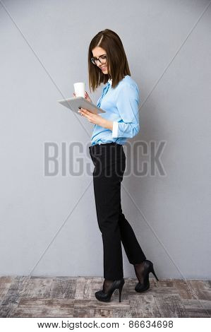 Full length portrait of a businesswoman with cup of coffee and tablet computer. Wearing in black pants and blue shirt.