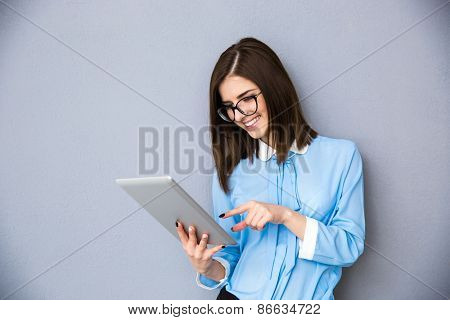 Smiling businesswoman using tablet computer over gray background. Wearing in blue shirt and glasses