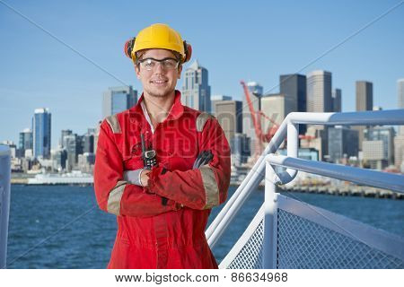 Docker and deck hand posing on the bridge of a ship, about to moor off in a city harbor, with the seattle skyline in the background