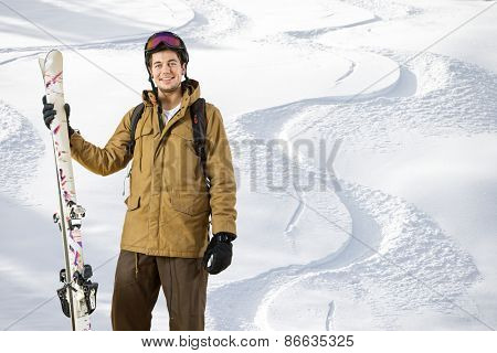 Young off piste skier standing in front of fresh tracks in the powder snow with skis in his hand