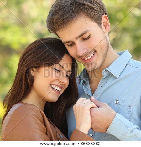 Couple Hugging And Holding Hands While Looks An Engagement Ring