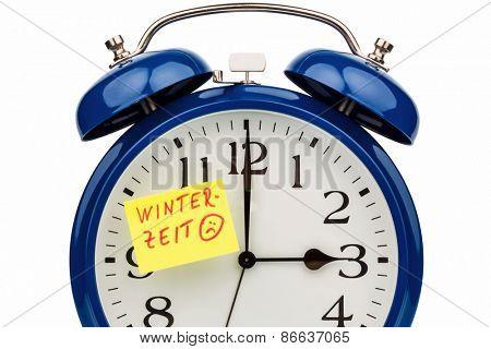 an alarm clock with a note as a reminder to the uhrumstellung zurwinterzeit