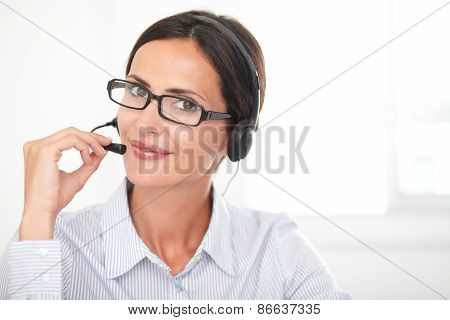 Adult Hispanic Secretary Talking On Headphones
