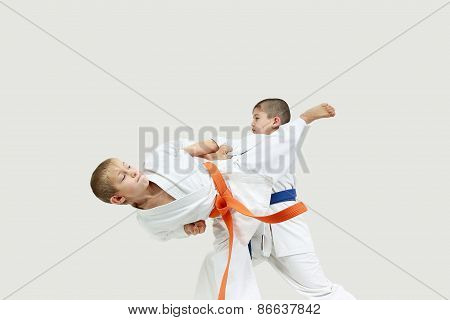 Boys in karategi are doing paired exercises karate