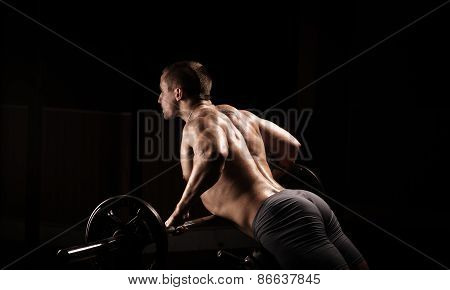 power athletic guy execute exercise with dumbbells in sport-hall