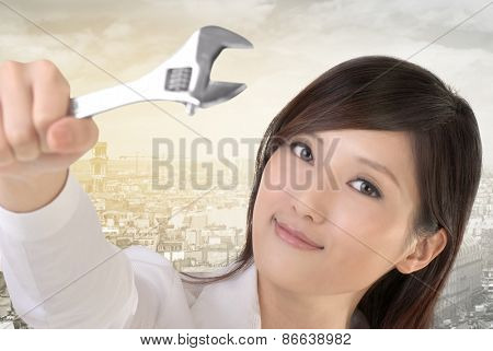 Business woman fix by using wrench.