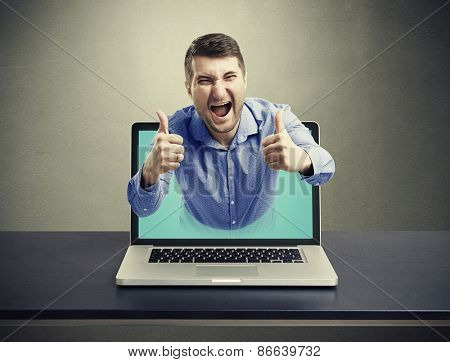 screaming happy man got out of the laptop and showing thumbs up against dark background