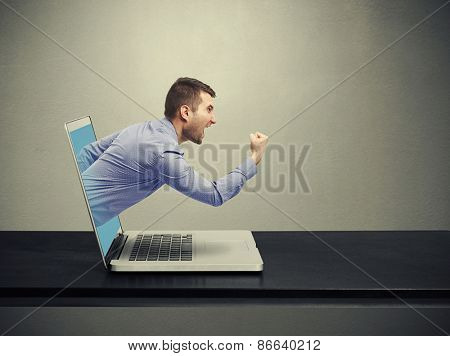 emotional businessman got out of the laptop and screaming over dark background