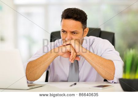 thoughtful middle aged businessman sitting in modern office
