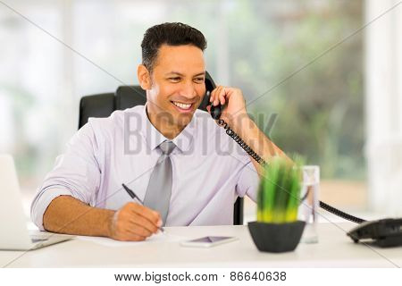 smiling middle aged businessman talking on landline phone and writing report