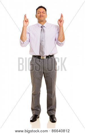 hopeful mid age man with fingers crossed isolated on white background