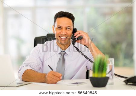 good looking mid age businessman making phone call