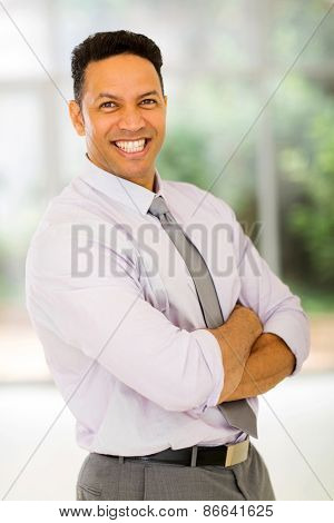 portrait of businessman with arms crossed in modern office