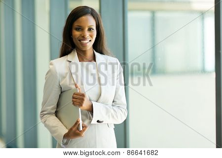 pretty young african office worker holding laptop