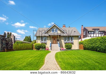Cozy house with beautiful landscaping on a sunny day