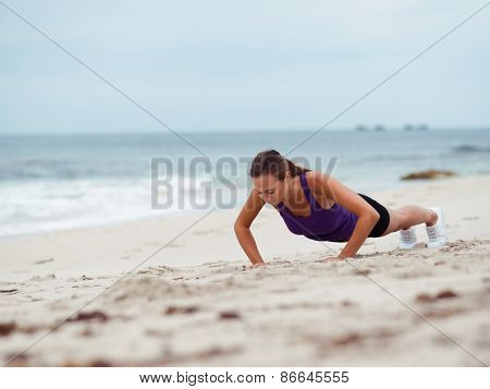 Sporty young woman doing push ups on the sea coast