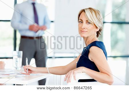 Businesswoman sitting and smiling at camera