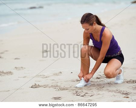 Sporty young woman doing her laces on the sea coast