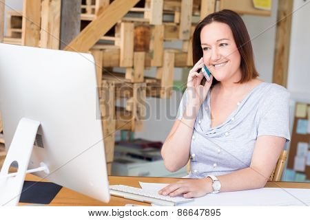 Woman in casual wear with his mobile in office