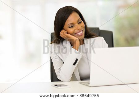 smiling african businesswoman looking at computer screen