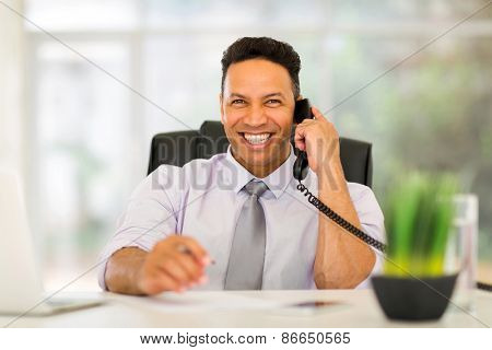 portrait of happy business executive talking on landline