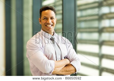 portrait of smiling mid age businessman in office building