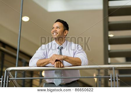 happy middle aged businessman looking up in office