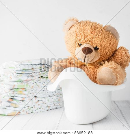 A teddy bear in a white potty next to stack of diapers.